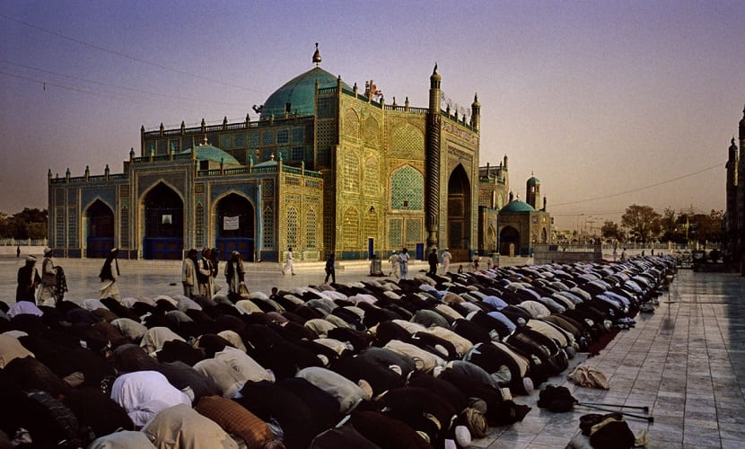 AFGHANISTAN. Herat. Mazar-E-Sharif. September 2008. A crowd of faithful people are praying at the courtyard of the complex of Shrine of Hazrat Ali, in the holy city of Mazar-E-Sharif. Afghan people think that the Imam Ali's body is buried here. Pilgrims come from across the country to pay their respects at the tomb contained inside. Talking about the fact that Afghanistan is coming back to life can be excessive, because half of the country is in ruins; poverty can be seen everywhere and living conditions for the vast majority are very hard. Thousands of widows and orphans survive begging or working as a shoeshine at the shabby streets of the cities.  While men queue at the barberÕs to have their beards shaved and go to the cinema, most women still wear burqa because they are afraid of tradition and their situation has hardly improved.